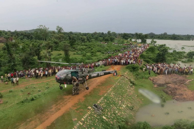 Flood-affected villagers gather as an Indian Army HAL Chetak helicopter hovers during a mission along the overflowing Betwa river in the Jhansi region. Army personnel were moved in to rescue villagers stranded due to floods in Betwa River in Jhansi region, according to a Ministry of Defence press release. (Getty Images)