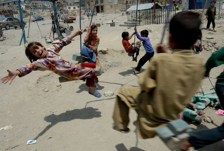 Afghan children play on a swing near a cemetery in Kabul. Civilian casualties in the Afghan war rose 23 percent in the first half of this year due to Taliban attacks and increased fighting between insurgents and government forces, the UN said on July 30. (Shah Marai/Getty Images)