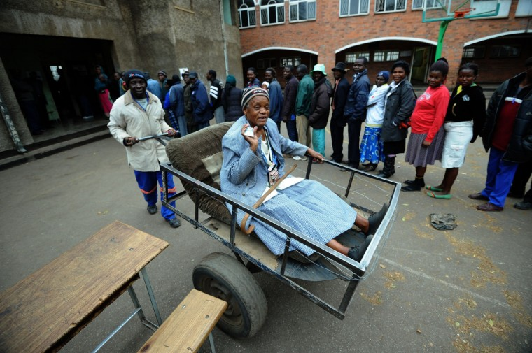 Zimbawean Chizema Najika (L), 80, shows her card as she leaves in a pass cart, after voting, a polling station where other people queue up in Harare. Zimbabwean vote today in a general election in Zimbabwe. Zimbabwe was readying for an inadequately prepared yet tight election battle that could see President Robert Mugabe extend his 33-year grip on power. From a list of five candidates, voters will chose who will lead the nation for the next five years after a compromise government forced by a crisis ignited by the 2008 presidential run off. But the real battle is between Mugabe and his perennial rival Prime Minister Morgan Tsvangirai. (Alexander Joe/Getty Images)