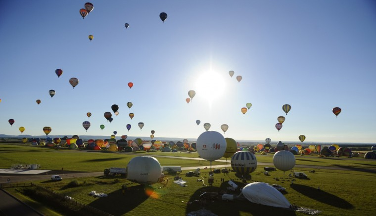 "Hot air-balloons fly over Chambley-Bussieres, to try to set a world record with 408 balloons in the sky, eastern France on July 31, 2013 as part of the yearly event ""Lorraine Mondial Air Ballons"", an international air-balloon meeting. (Jean-Christophe Verhaegen/Getty Images)"