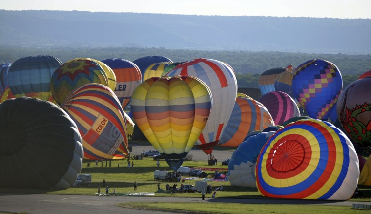"Hot air-balloons take off from Chambley-Bussieres, to try to set a world record with 408 balloons in the sky, eastern France on July 31, 2013 as part of the yearly event ""Lorraine Mondial Air Ballons"", an international air-balloon meeting. (Jean-Christophe Verhaegen/Getty Images)"