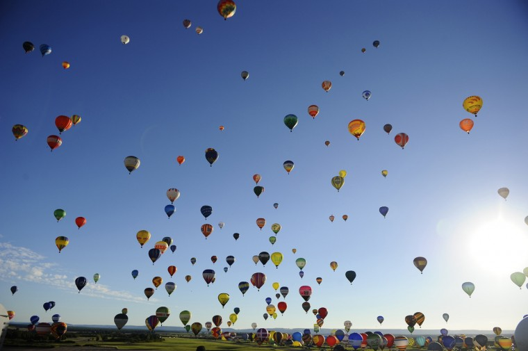 "Hot-air balloons fly over Chambley-Bussieres, eastern France, to try to set a world record with 408 balloons in the sky, on July 31, 2013, as part of the yearly event ""Lorraine Mondial Air Ballons"", an international air-balloon meeting. (Jean-Christophe Verhaegen/Getty Images)"