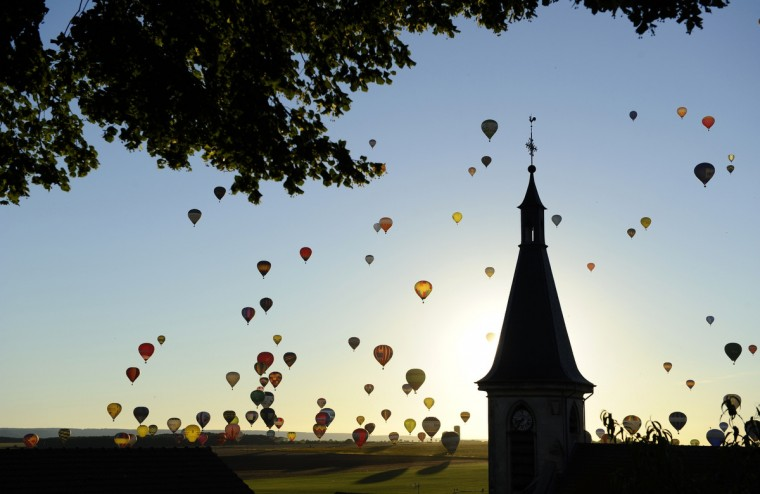 "Hot-air balloons fly near a church over Chambley-Bussieres, eastern France, on July 31, 2013 at sunset, to try to set a world record with 408 balloons in the sky, as part of the yearly event ""Lorraine Mondial Air Ballons"", an international air-balloon meeting. (Jean-Christophe Verhaegen/Getty Images)"