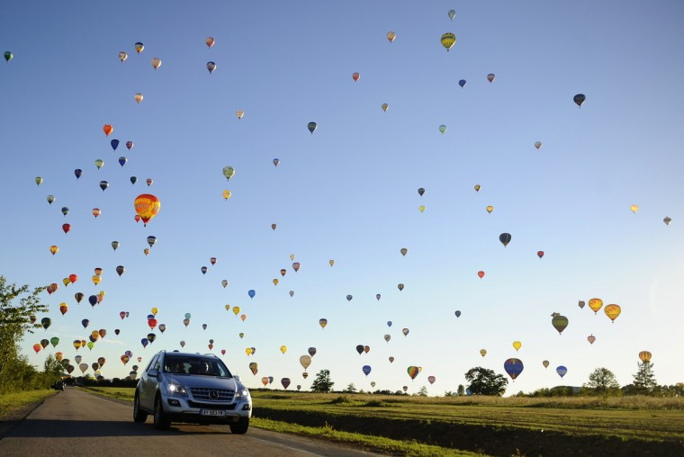 "A car drives on a road while hot-air balloons fly over Chambley-Bussieres, eastern France, on July 31, 2013, to try to set a world record with 408 balloons in the sky, as part of the yearly event ""Lorraine Mondial Air Ballons"", an international air-balloon meeting. (Jean-Christophe Verhaegen/Getty Images)"
