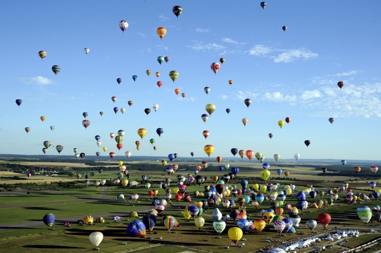 "Hot air-balloons take off from Chambley-Bussieres, eastern France, to try to set up a world record with 408 balloons in the sky on July 31, 2013, as part of the yearly event ""Lorraine Mondial Air Ballons"", an international air-balloon meeting. (Alexandre Marchi/Getty Images)"