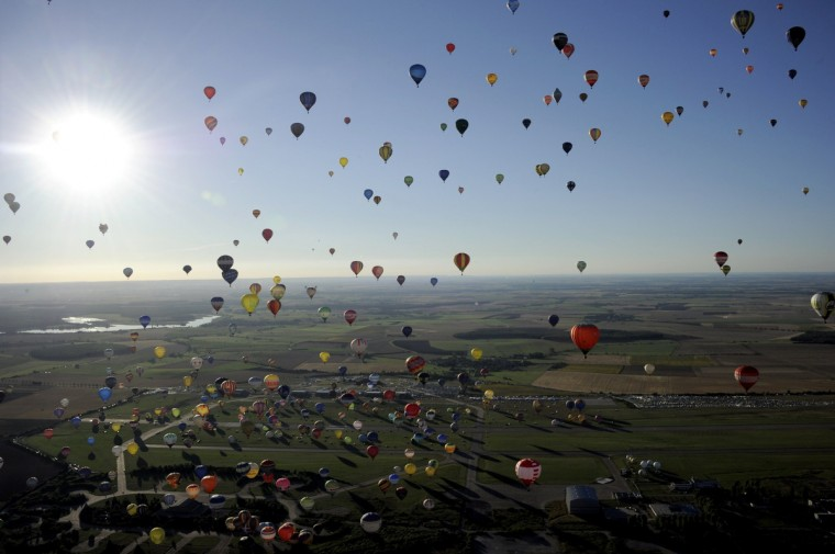 "Hot air-balloons fly over Chambley-Bussieres, eastern France, to try to set up a world record with 408 balloons in the sky on July 31, 2013, as part of the yearly event ""Lorraine Mondial Air Ballons"", an international air-balloon meeting. (Alexandre Marchi/Getty Images)"