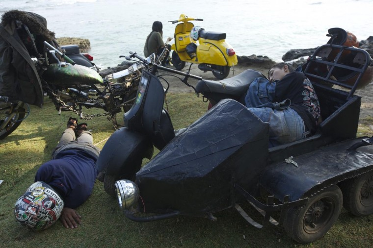 Vespa enthusiasts sleep near their heavily modified scooters during a scooter festival on June 30, 2013 in Cibeureum, about 100 km west of Jakarta, Indonesia. (Ed Wray/Getty Images)