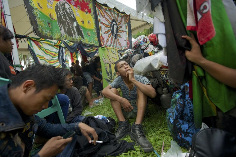 Vespa enthusiasts smoke near a tent selling Bob Marley cloths and scooter equipment during a scooter festival on June 30, 2013 in Cibeureum, about 100 km west of Jakarta, Indonesia. (Ed Wray/Getty Images)