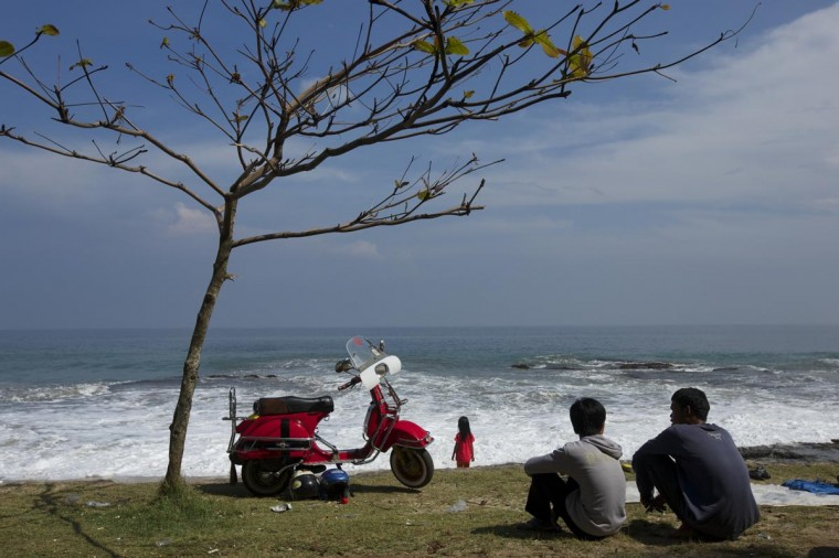 Vespa enthusiasts sit at the beach during a scooter festival on June 30, 2013 in Cibeureum, about 100 km west of Jakarta, Indonesia. (Ed Wray/Getty Images)