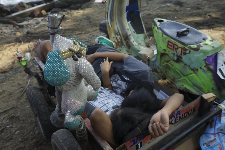 Vespa enthusiasts sleep in heavily modified scooters during a scooter festival on June 30, 2013 in Cibeureum, about 100 km west of Jakarta, Indonesia. (Ed Wray/Getty Images)