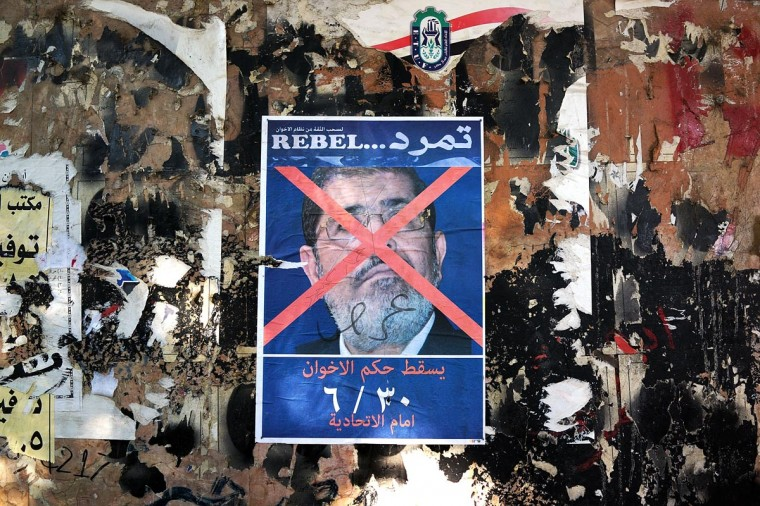 An anti-President Mohammed Morsi poster is viewed as as thousands of Egyptian protesters celebrate in Tahrir Square as the deadline given by the military to Egyptian President Mohammed Morsi passes on July 3, 2013 in Cairo, Egypt. (Spencer Platt/Getty Images)