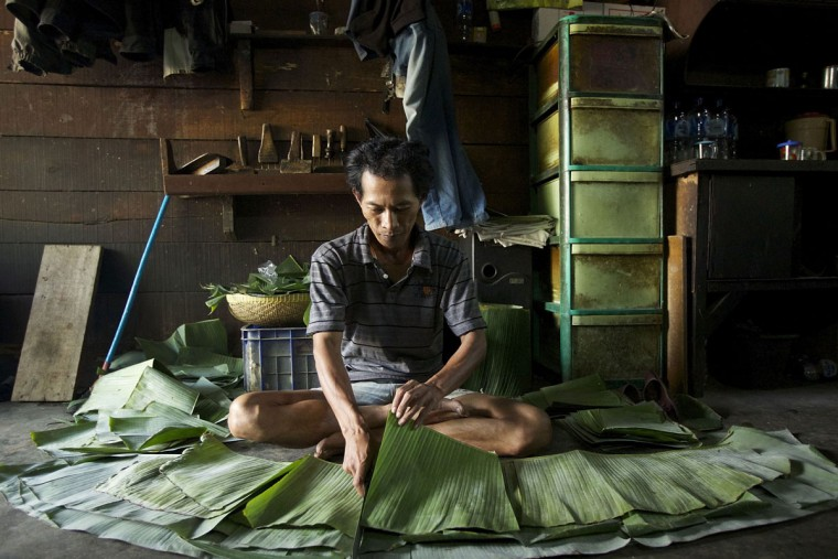 A man cuts banana leaves in which to wrap fermented soy beans at a small tempeh factory on July 12, 2013 in Jakarta, Indonesia. Tempeh is an Indonesian staple made from fermented soy beans. The Indonesian government has said that it will increase food imports during the Ramadan fasting month to reduce inflation caused by increased food consumption during the month leading up to and during the Eid Al Fitr holiday marking the end of the fasting month. (Ed Wray/Getty Images)