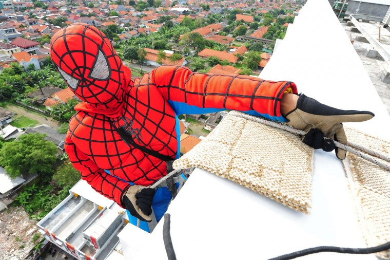 Indonesian 'Spider-Man' window cleaner, 37-year-old Teguh prepares to clean the glass windows of the 18-story Alana Hotel on July 12, 2013 in Surabaya, Indonesia. Teguh is a specialist glass window cleaner working on high-rise buildings wearing a Spider-Man uniform and working at an altitude of over 500 meters above ground level. He earns between Rp. 5 million and 15 million depending on the height of the building and the level of difficulty. (Robertus Pudyanto/Getty Images)