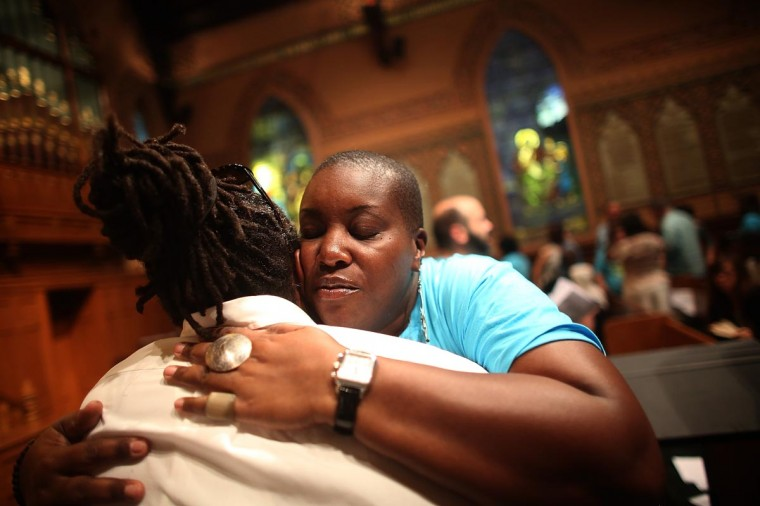 People hug during services at Middle Collegiate Church in Manhattan honoring Trayvon Martin on July 14, 2013 in New York City. George Zimmerman was acquitted of all charges in the shooting death of Martin July 13 and some congregants wore hoodies during the service to honor Martin. (Mario Tama/Getty Images)