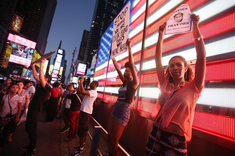 Trayvon Martin supporters stand in front of a lighted American flag in Times Square after marching from a rally for Martin in Union Square in Manhattan on July 14, 2013 in New York City. (Mario Tama/Getty Images)