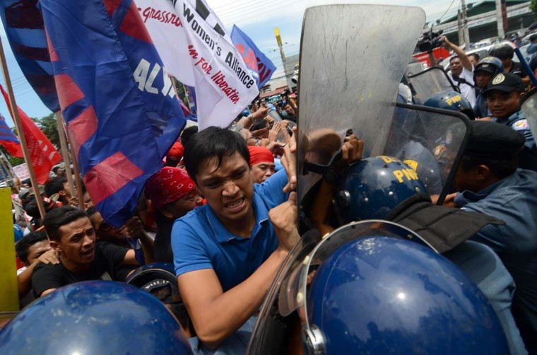 Anti-government protestors scuffle with riot police during Philippine president Benigno Aquino III's State of the Nation Address on July 22, 2013 in Quezon City, Philippines. Thousands of protestors tried to break through police barriers to get near the House of Representatives where Aquino is speaking before the Upper and Lower House of the Philippine Congress. (Dondi Tawatao/Getty Images)