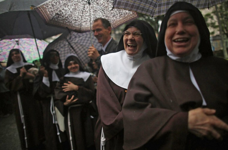 Nuns from the Nossa Senhora dos Anjos monastery wait in line in the rain to attend Pope Francis' visit to the Hospital de Sao Francisco de Assis (Hospital of Saint Francis of Assisi) on July 24, 2013 in Rio de Janeiro, Brazil. The nuns rarely leave the monastery. (Mario Tama/Getty Images)