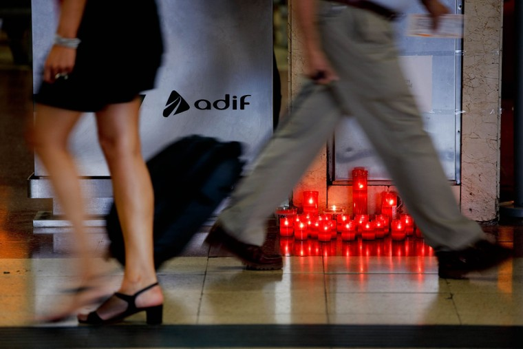 """Passengers walk past a memorial altar composed by a sign decorated with a black bow and a sentence which says """"In memory of our colleagues Olga and David"""" remembering ADIF workers death on the high-speed train crash in Santiago de Compostela at Chamartin Train Station on July 26, 2013 in Madrid, Spain. (Gonzalo Arroyo Moreno/Getty Images)"""