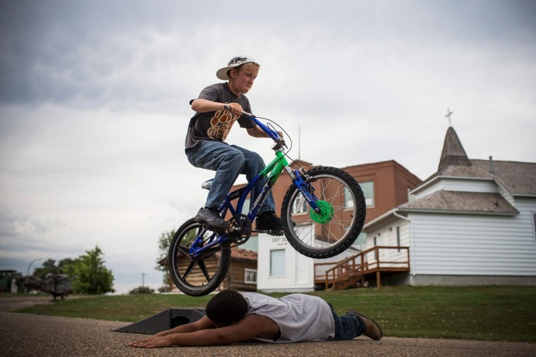 Fielding (on bike), jumps over Zach on July 28, 2013 in Alexander, North Dakota. Fielding's dad, who works as a mechanic and welder, moved the family to North Dakota from Mexico after learning of work being offered. North Dakota has been experiencing an oil boom in recent years, due in part to new drilling techniques including hydraulic fracturing and horizontal drilling. (Andrew Burton/Getty Images)