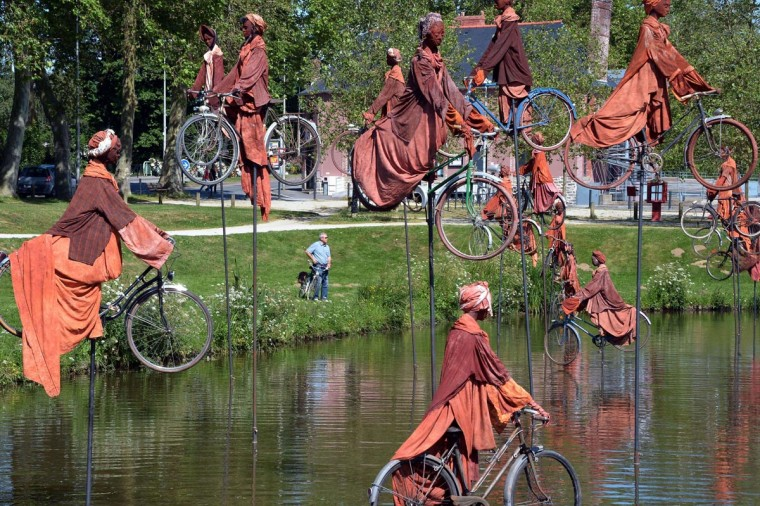 "A photo taken on July 1, 2013 shows a sculpture by French artist Guy Lorgeret, entitled ""Retour a Betton"" (""Return to Betton""), in Betton, a suburb of the western French city of Rennes. The sculpture represents people on bicycles migrating from a bank to another, claiming their freedom, like their refusal to compete. (Damien Meyer/AFP/Getty Images)"