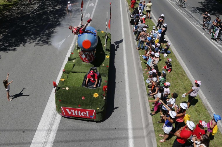 A woman sprays water on spectators from a Vittel vehicle belonging to the Tour de France advertising caravan before the start of the 25 km team time-trial and fourth stage of the 100th edition of the Tour de France cycling race on July 2, 2013 around Nice, southeastern France. (Joel Saget/AFP/Getty Images)