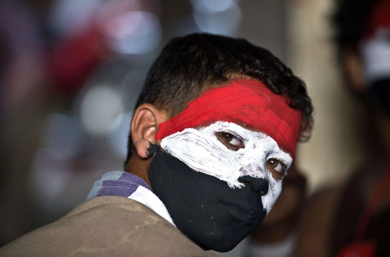 An Egyptian youth with his face painted in the colours of the national flag look over as opponents of Egyptian President Mohamed Morsi protest calling for his ouster at Cairo's landmark Tahrir Square, on July 2, 2013. (Khaled Desouki/AFP/Getty Images)