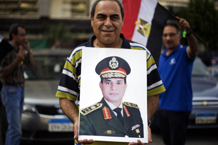 An Egyptian protester holds a poster bearing the portrait of Egyptian Defense Minister Abdelfatah al-Sisi outside the Ministry of Defense in Cairo on July 3, 2013, during a demonstration against President Mohamed Morsi and the Muslim Brotherhood. (Gianluigi Guercia/AFP/Getty Images)