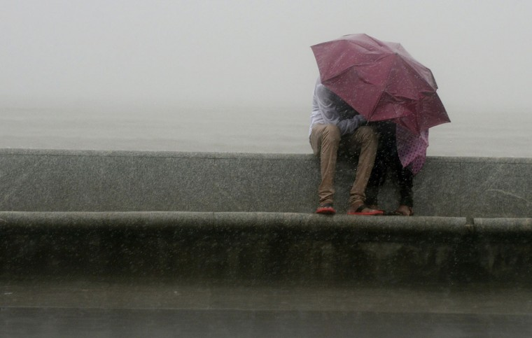 An Indian couple sit together under an umbrella during heavy rain showers at the sea front in Mumbai on July 12, 2013. The monsoon season, which runs from June to September, accounts for about 80 percent of India's annual rainfall, vital for a farm economy which lacks adequate irrigation facilities. (Punit Paranjpe/AFP/Getty Images)