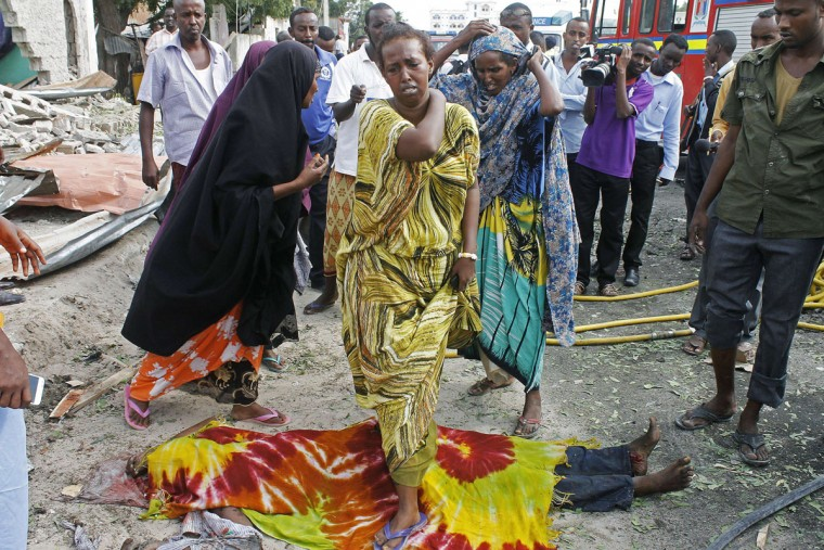 Somali women walk over dead bodies covered by blankets after a suspected suicide bomber rammed a car laden with explosives into an armored convoy of African Union troops in Mogadishu on July 12, 2013. Initial reports from witnesses near the blast said a car targeted AU troops on a busy street close to the central K4 roundabout, while an AFP reporter confirmed a loud blast followed by heavy gunfire. (Mohamed Abdiwahab/AFP/Getty Images)