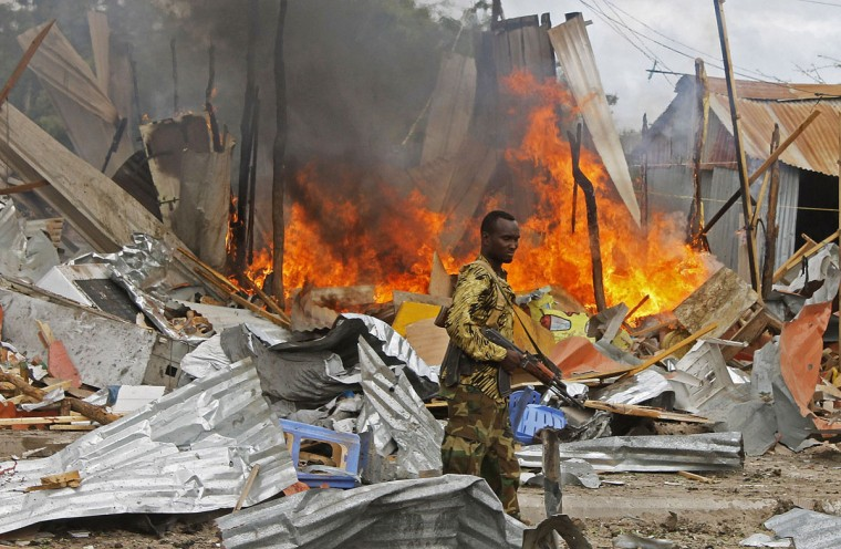 A Somali National Government (SNG) soldier walks past burning debris after a suspected suicide bomber rammed a car laden with explosives into an armored convoy of African Union troops in Mogadishu on July 12, 2013. Initial reports from witnesses near the blast said a car targeted AU troops on a busy street close to the central K4 roundabout, while an AFP reporter confirmed a loud blast followed by heavy gunfire. (Mohamed Abdiwahab/AFP/Getty Images)