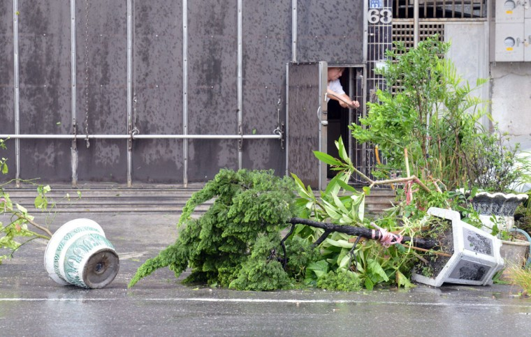"A local resident locks his home as his plants are blown down by typhoon Soulik in Ilan, eastern Taiwan on early July 13, 2013. Thousands of people were evacuated in Taiwan and the entire island declared an ""alert zone"" as Typhoon Soulik made landfall early morning, killing one person and injuring seven. (Sam Yeh/AFP/Getty Images)"