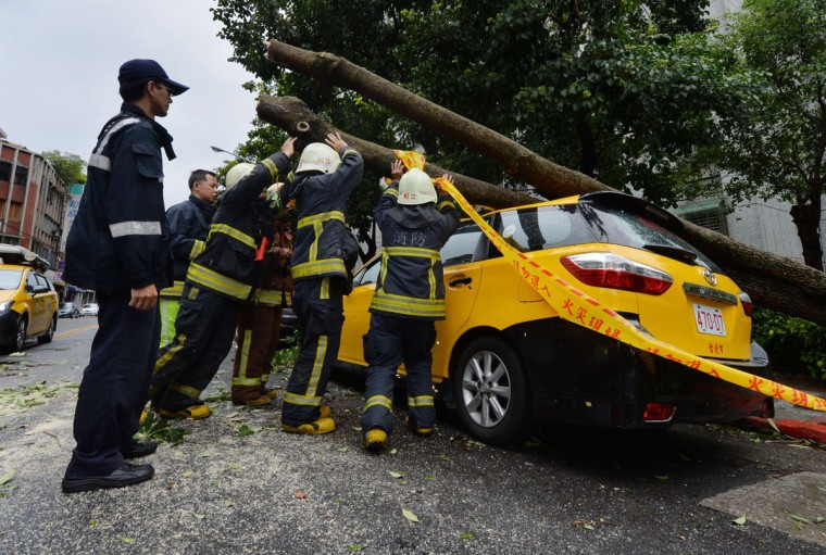 "Police and firemen attempt to remove a tree that crushed a taxi after Typhoon Soulik hit Taipei on July 13, 2013. Thousands of people were evacuated in Taiwan and the entire island declared an ""alert zone"" as Typhoon Soulik made landfall. (Mark Ralston/AFP/Getty Images)"
