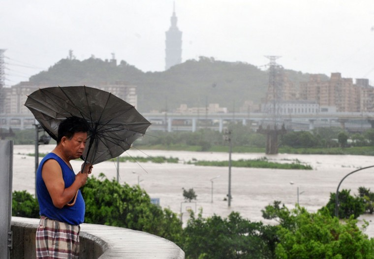 "A resident battles against strong winds caused by typhoon Soulik in Taipei on July 13, 2013. Thousands of people were evacuated in Taiwan and the entire island was declared an ""alert zone"" as Typhoon Soulik made landfall. (Mandy Cheng/AFP/Getty Images)"