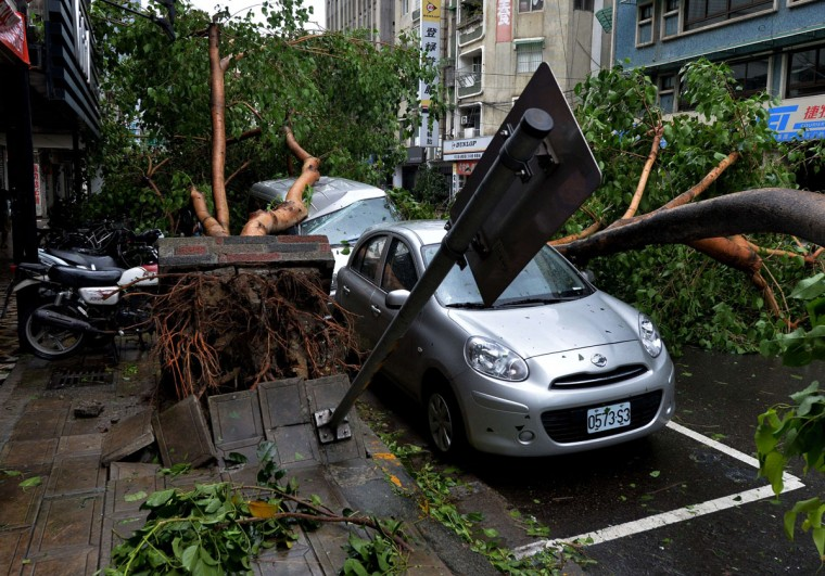 "Vehicles damaged by fallen trees after Typhoon Soulik hit Taipei on July 13, 2013. Thousands of people were evacuated in Taiwan and the entire island declared an ""alert zone"" as Typhoon Soulik made landfall. (Mark Ralston/AFP/Getty Images)"