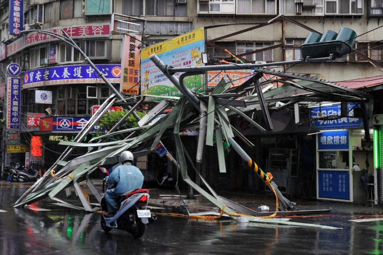 "A motorcycle drives past a damaged tin roof and traffic signs caused by typhoon Soulik in Taipei on July 13, 2013. Thousands of people were evacuated in Taiwan and the entire island declared an ""alert zone"" as Typhoon Soulik made landfall early morning. (Mandy Cheng/AFP/Getty Images)"