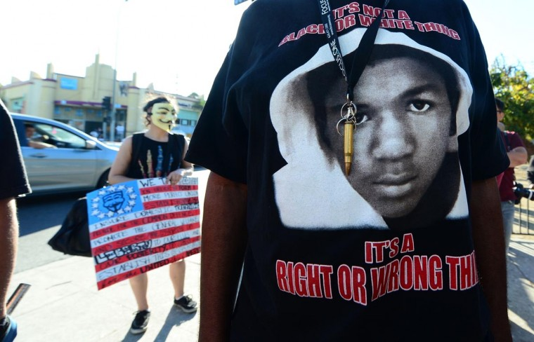 A man wears a single bullet around his neck over his Trayvon t-shirt as people hold placards and shout slogans during a rally in Los Angeles on July 15, 2013. (Frederic J. Brown/AFP/Getty Images)