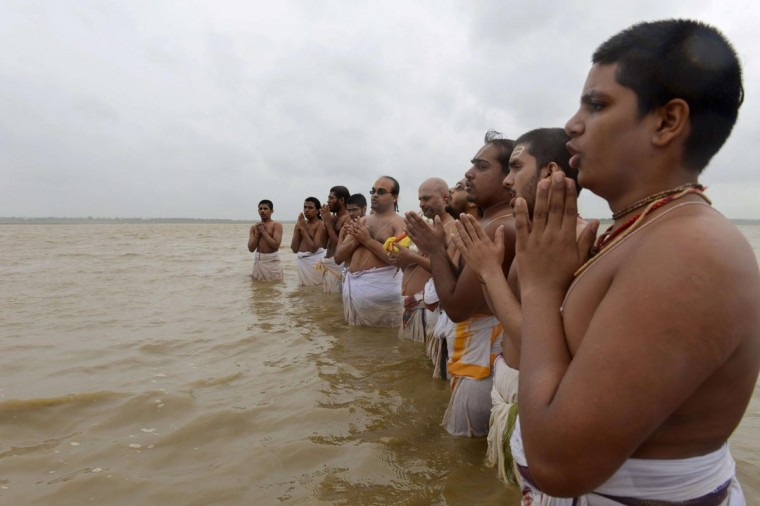 Indian Hindu priests from the Chilkur Balaji Temple offer prayers for monsoon rains (Varuna japam) as they stand in the Osman Sagar Lake in Hyderabad on July 16, 2013. The monsoon rains which usually hit India from June to September are crucial for farmers whose crops feed hundreds of millions of people. (Noah Seelam/AFP/Getty Images)