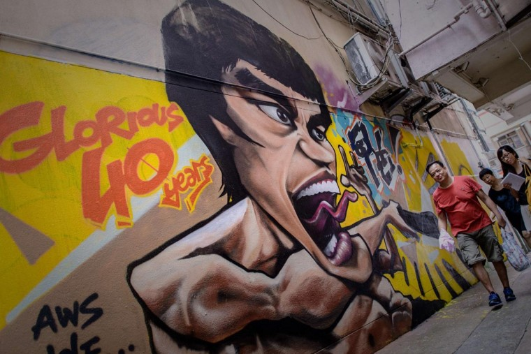 A man walks past graffiti depicting the late martial arts icon Bruce Lee in Hong Kong on July 16, 2013. Hong Kong will mark the death of the late Kung Fu and movie star on July 20, 40 years after his death. (Philippe Lopez/AFP/Getty Images)