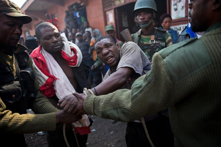 A man accused by the Congolese Army of being a spy of rebels of the M23 movement is tied and taken away on July 16, 2013 in Munigi on the outskirts of Goma in the east of the Democratic Republic of the Congo. The army in the Democratic Republic of Congo on July 16 pursued an offensive against rebels of the M23 movement to protect the North Kivu provincial capital of Goma. (Phil Moore/AFP/Getty Images)