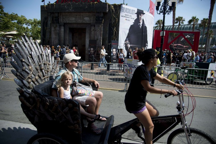 A man and his daughter ride through the San Diego Gaslamp District in a pedicab especially decorated for Comic-Con International 2013 in San Diego California July 18, 2013. (Robyn Beck/AFP/Getty Images)