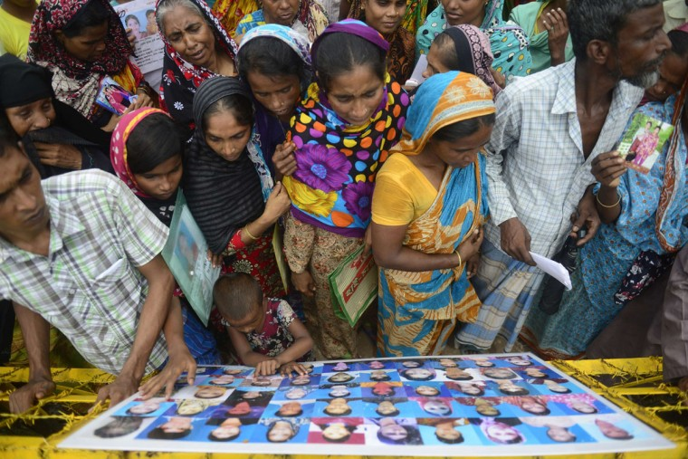 Bangladeshi family members and supporters look at a photographic installation of portraits of garment workers on the three-month anniversary of the collapse of a nine-story building collapse in Savar, on the outskirts of Dhaka on July 24, 2013. Hundreds of garment workers staged demonstrations at the site of Bangladesh's worst industrial disaster, demanding compensation for the survivors and a full account of the missing laborers of the April 24, 2013 factory building collapse that killed 1,129 people.(Munir uz Zaman/AFP/Getty Images)