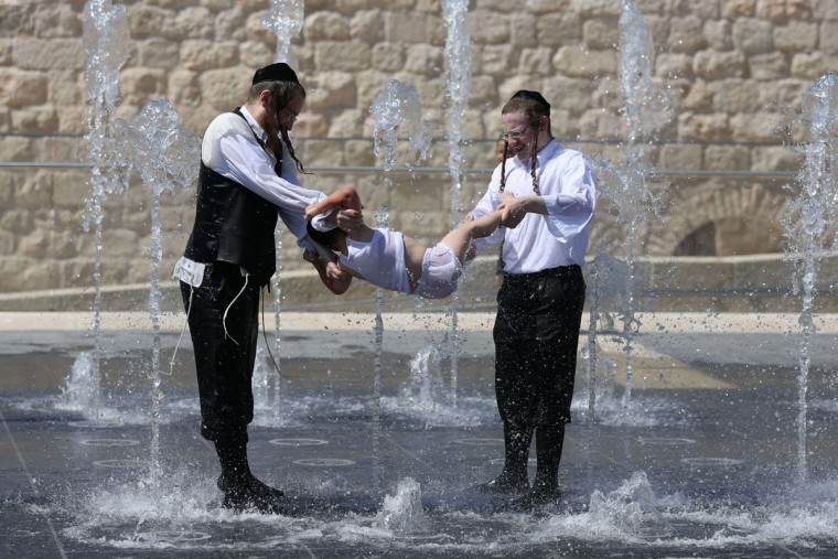 Ultra-orthodox Jews cool themselves in a water fountain in Jerusalem next to the Old City walls as orthodox Yeshiva students enjoy Bein Hazmanim (between the times) summer vacation. (Menahem Kahana/AFP/Getty Images)