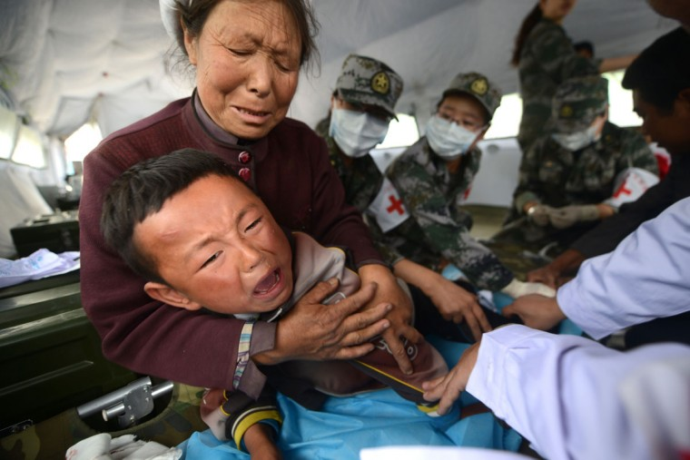 A boy cries as he receives treatment in a temporary shelter set up for quake victims in the town of Minxian in Dingxi, northwest China's Gansu province on July 24, 2013. At least 94 people were killed, China's official news agency reported citing local authorities on July 23, with 1,000 more injured and 51,800 homes collapsing. (Wang Zhao/AFP/Getty Images)