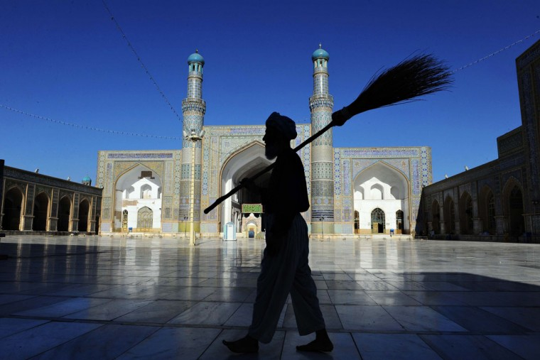 An Afghan sweeper carries his broom as he walks past the main mosque during the month of Ramadan in Herat on July 24, 2013. (Aref Karimi/AFP/Getty Images)