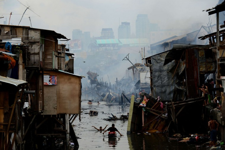 Residents wade through water searching for salvageable materials after a fire razed a slum area in Manila on July 24, 2013. Almost 200 houses were destroyed, leaving 400 residents homeless, according to a local media report. (Noel Celis/AFP/Getty Images)