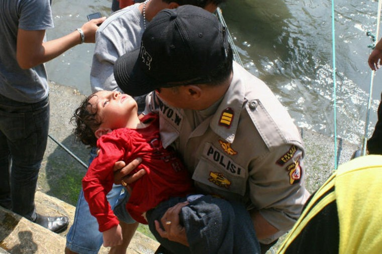 """An Indonesian policeman carries an exhausted young boy following more rescue by a search and rescue team in Cidaun, West Java on July 24, 2013. Rescuers searched the seas off Indonesia's Java island on July 24 for possibly dozens of asylum-seekers missing after their Australia-bound boat sank, leaving at least three dead, with 157 saved, an official said. Local rescue officials estimated there could have been """"up to 200"""" passengers on the boat which was bound for Australia, while a survivor said some 250 had boarded the vessel. (AFP/Getty Images)"""