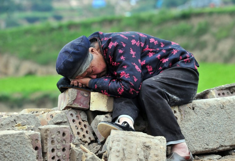 This picture taken on July 23, 2013 shows an elderly woman resting on the ruins after she lost her home during the earthquake in Minxian county in Dingxi, northwest China's Gansu province. The traumatised survivors of two shallow earthquakes that killed at least 94 people in China began burying their dead on July 23, as they struggled with the devastation left behind. (STR/AFP/Getty Images)