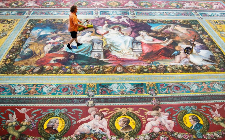 A conservator walks over a curtain on July 24, 2013 in the painting workshop of the Semper Opera House in Dresden, Germany. The curtain was reconstructed in 1984 after the original design by Ferdinand Keller and now needs to be cleaned after almost 30 years. The original from 1878 was burned in the bombing of Dresden on February 13,1945. (Hannibal Hanschke/AFP/Getty Images)