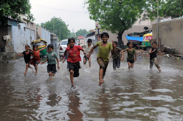 Indian children run across a flooded street in Ahmedabad on July 24, 2013. Heavy rains lashed many regions of Gujarat state and the Indian Meteorological Department (IMD) has warned of very heavy rains in Gujarat and surrounding regions in next 36 hours. (Sam Panthaky/AFP/Getty Images)