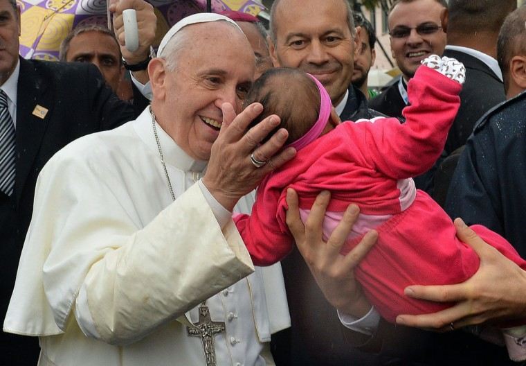 Pope Francis kisses a baby during his visit to the Varginha favela in Rio de Janeiro, on July 25, 2013. The Varginha favela is a community of 1,000 people which for decades was under the sway of narco-traffickers until it came under police control less than a year ago. (Luca Zennaro/Pool/AFP/Getty Images)